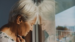 hopeless elderly woman, feeling loneliness during the lockdown. Vulnerable group and mental health issues. High quality photo
