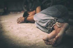 hopeless man hands tied together with rope, human trafficking