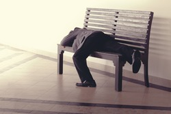 Hopeless stress businessman lay on bench with tired and loose from work