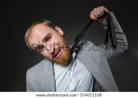 Hopeless stressed businessman with beard in grey suit hanging himself on tie over grey background #354011108