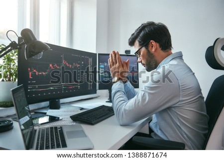 Hoping for the success. Side view of tired young businessman or trader holding palms together while working with data and charts on computers at his modern office.