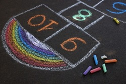 Hopscotch drawn with colorful chalk on asphalt outdoors