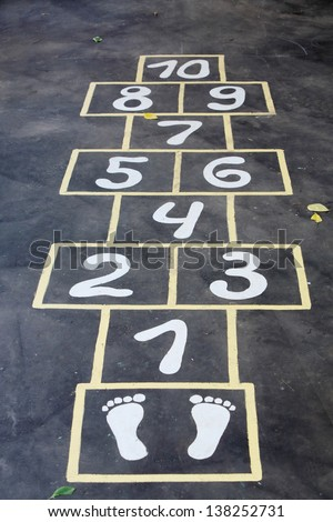 Hopscotch painted indelible ink on black asphalt for children outdoor.