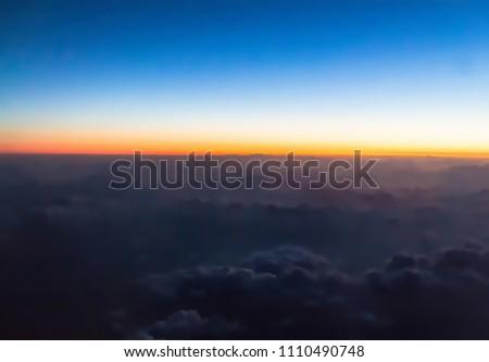 Horizon line of orange sky. Flight over clouds at beautiful golden orange sunset time or light sunrise. Foto stock ©