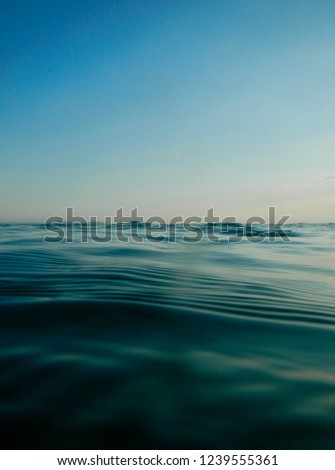 Horizon meets water, ocean rippled water meets sky, seascape of calm water clear sky, cloudless blue sky