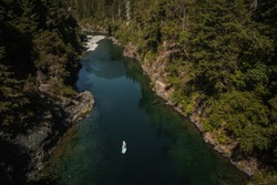 Horizontal aerial picture paddle boarder on standup paddle board paddling up river in summer exploring wild nature on remote river. Leisure sport recreation in idyllic Smith River northern California