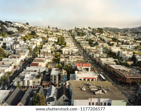 Horizontal aerial view of The Castro District neighborhood synonymous with gay culture in Eureka Valley. Flyover typical Victorian houses rolling hills cityscape, tightly packed residential homes