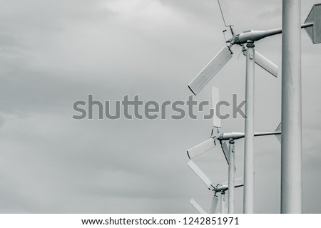 Horizontal axis wind turbine with grey sky and clouds. Wind energy in eco wind farm. Green energy concept. Renewal energy. Alternative electricity source. Sustainable resources. #1242851971