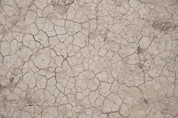 Horizontal background shot of a barren, cracked patch of land with no vegetation. Crusty, dry land, affected by drought, a dramatic impact on the environment.