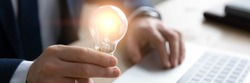 Horizontal banner close up successful businessman holding light bulb, inspiration and creativity concept, innovative business startup idea, motivated executive or boss working on creative project