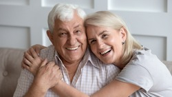 Horizontal banner happy old couple in love seated on couch embracing, laughing grey haired husband and wife pose looks at camera, elderly family portrait, long life marriage, sincere feelings concept