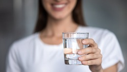Horizontal banner image, on foreground caucasian female hand holds glass of clear water give to camera smiling selective close up focus. Concept of healthy lifestyle, beauty skin health care treatment