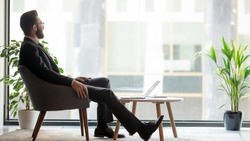 Horizontal banner middle eastern ethnicity businessman sit on armchair resting in modern room looks out window thinking about prosperous his own company plan future projects, business vision concept