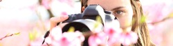 Horizontal banner of a woman photographing flowers with dslr camera and macro lens in a field