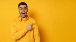 Horizontal banner of surprised man feeling shocked about beneficial commercial offer, pointing to copy space on right, screaming WOW, isolated on yellow background