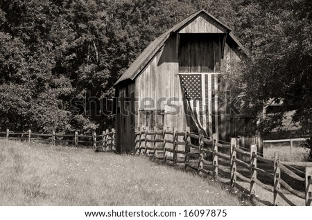Horizontal black and white photo of old wooden barn with fluttering US flag