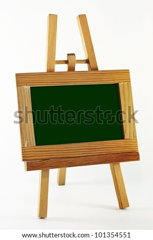 Horizontal blank green chalkboard space in wooden frame on easel isolated on white.