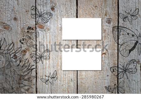 Horizontal business card mockup over natural wood deck table background. Card is 50x90mm. Wood deck have doodle pictures with sunflowers and butterflies.