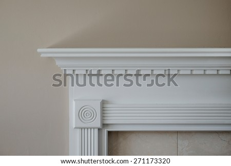 Horizontal capture of corner of white mantle and marble trim against beige wall in natural light.