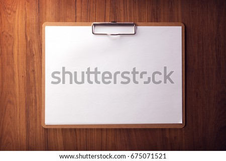 Horizontal clipboard with blank white paper on wooden surface. Retro muted tone.  Low key.