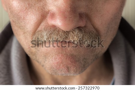 horizontal close up  image of a  caucasian man\'s face from the nose to bottom of chin  with mustache and facial hair.