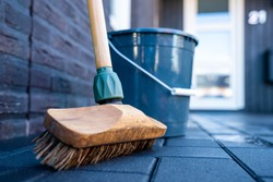 Horizontal close-up image of broom Cleaning dark concrete block floor driveway in front of a modern house. Scrubbing the service with a detergent with foam and water. Spring cleaning of the driveway.