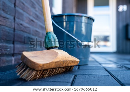 Horizontal close-up image of broom Cleaning dark concrete block floor driveway in front of a modern house. Scrubbing the service with a detergent with foam and water. Spring cleaning of the driveway.  ストックフォト ©