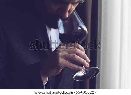 horizontal close up of a Caucasian man with beard, black suit and white shirt tasting a glass of red wine