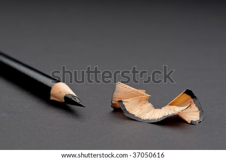 Horizontal close up of a sharpened black pencil with shavings