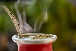 Horizontal Close-Up Of Hot Traditional South American, Caffeine-Rich Infused Drink Mate (Yerba Mate) In A Red Ceramic Gourd. Steaming Mate Infusion In A Modern Red Cup Against Greenery Background