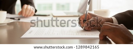 Horizontal close up photo african businessman sitting at desk holds pen signing contract paper, lease mortgage, employment hr or affirm partnership agreement concept, banner for website header design