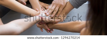Horizontal close up photo young people girls and guys hold stack hands together high five gesture symbol of support trust and common goal teamwork and success concept, banner for website header design