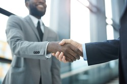 Horizontal close up shot of two unrecognizable modern businessmen shaking their hands, copy space