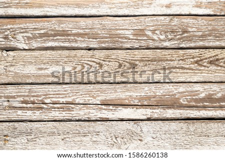 Horizontal closeup of an old wooden plank planks with a worn layer of white paint and cracks from weather and time. Light vintage background made of natural material.