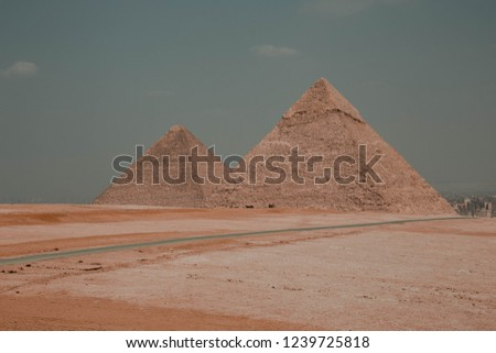 Horizontal colour image of 2 of 3 great  Giza Pyramids (Khufu and Kafre) taken from the western part in Sahara. (No People) captured in Sep 2018, Giza, Egypt.