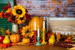 horizontal fall scene with autumn flowers orange pumpkins and burning candles for thanksgiving with no people