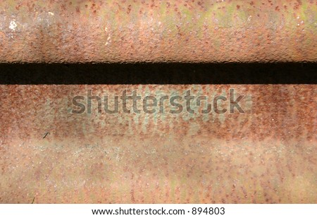 Horizontal fold on rusty metal sheet.