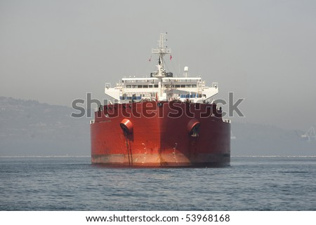 "Horizontal front view image of a red Ultra Large Crude Carrier, or ""Super Tanker.""  These vessels are capable of carrying up to two million barrels of oil across the seas."