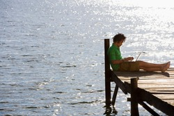Horizontal full length profile shot of a solitary young man sitting on a jetty beside the lake using a laptop.