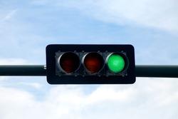 Horizontal Green Traffic Light Against Noon Day Sky
