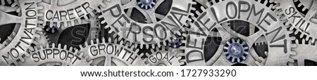 Horizontal group of tooth wheels with Personal Development, Motivation, Goal, Career and Support concept related words imprinted on metal surface