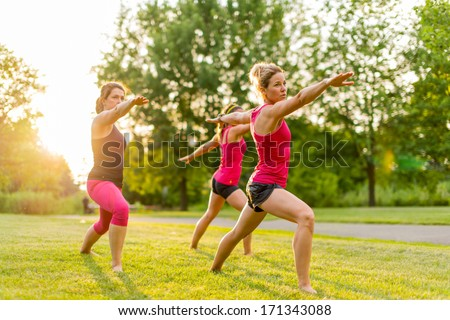 horizontal group of women doing the warrior yoga pose outdoors at sunset with lens flare
