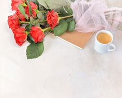 Horizontal holliday composition with cup of coffee, red rosses bouquet and notebook on a white texture background with copy space for text. Holliday morning. The concept of love and dating