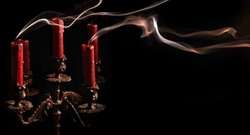 Horizontal image blown candle with line of smoke in massive bronze candlestick