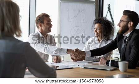 Horizontal image different ethnicity businessmen shaking hands sitting at conference room desk starting negotiating solving common issues planning future cooperation, company boss greet client concept