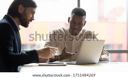 Horizontal image multi-ethnic businessmen looking at laptop screen discussing sales stats using new application business program, express opinion sharing thoughts working together on project concept