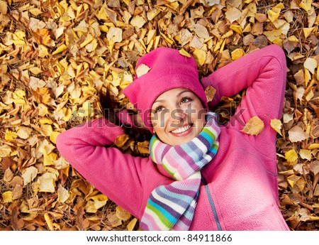 Horizontal image of a beautiful young woman lying in a pile of leaves.