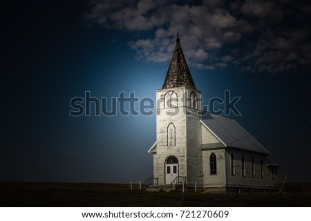horizontal image of a bright light shining on an old white country church in the late evening and night time. #721270609