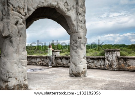 horizontal image of a caucasian woman on vacation leaning against an old stone wall under a big stone archway gazing across the green hills and trees #1132182056