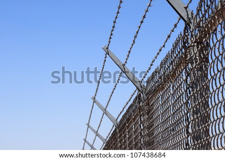 horizontal image of a chain link security fence topped with three strands of barbed wire and blue sky background